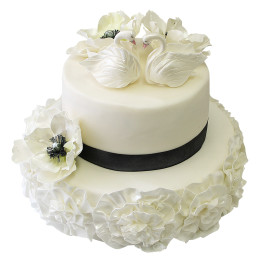 White bunk wedding cake with dark ribbon, flowers and swans