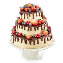 Festive cake in three tiers decorated with raspberries, blueberries and strawberries