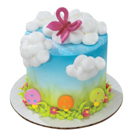Cake children's summer day with figures of colorful trees and clouds of whipped cream