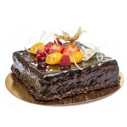 Праздничный торт в один ярус квадратной формы покрыт темным шоколадом и свежими ягодами малины клубники и смородины