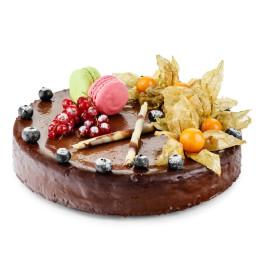 Праздничный торт в один ярус покрыт темным шоколадом и свежими ягодами физалиса, голубики, смородины и макарунами