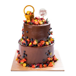 Торт в два яруса украшенный свежими ягодами клубники, голубики и малины покрытие из темного шоколада