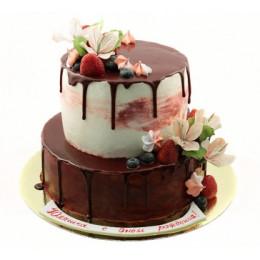 Торт в два яруса украшенный свежими ягодами клубники, голубики и цветами