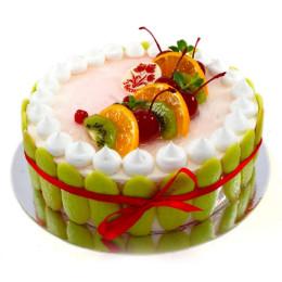 Праздничный торт в один ярус покрытый белым кремом украшен свежими ягодами клубники, киви, дольками апельсина