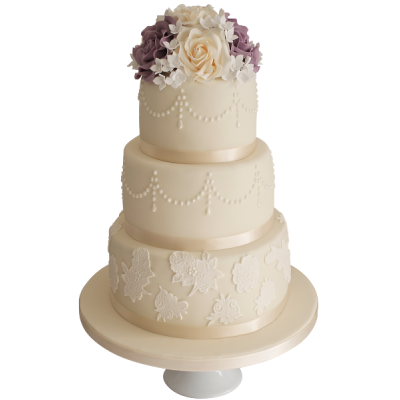 Белый трехъярусный свадебный торт с множеством цветов на верхнем ярусе