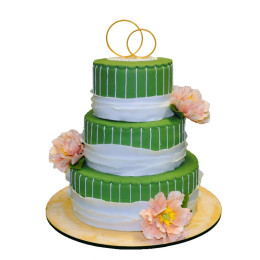 Three tiered wedding cake in green decorated with lush buds of fresh flowers and figurines of wedding rings
