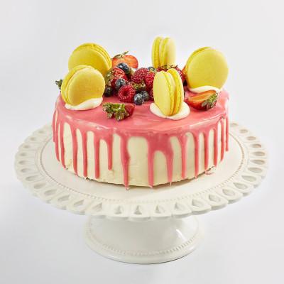 Открытый торт украшен свежей клубникой макарунами и розовой глазурью