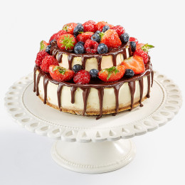 Открытый торт в два яруса украшен свежими ягодами клубники, черники
