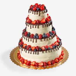 Открытый торт в четыре яруса украшен свежими ягодами клубники, черники